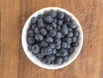 Blueberries in ceramic cup. On wooden cutting board Royalty Free Stock Photo