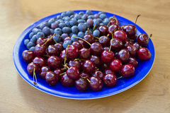 Blueberries and cherries lay on blue plate Stock Photo
