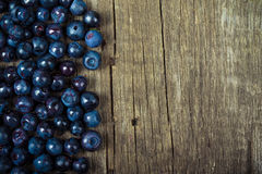 Blueberries collected manually scattered on the old board Stock Image