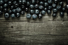 Blueberries collected manually scattered on the old board. Royalty Free Stock Images