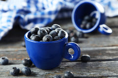 Blueberries in cup on a blue wooden background Royalty Free Stock Photo