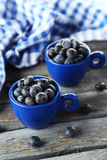 Blueberries in cup on a blue wooden background Royalty Free Stock Photos