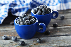 Blueberries in cup on blue wooden background. Royalty Free Stock Photo