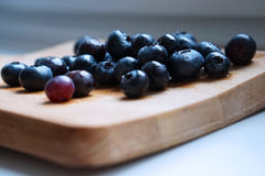 Blueberries. Fresh wet blueberries on wood surface Stock Photos