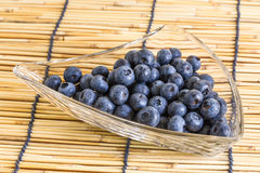 Blueberries in the glass bowl on the wooden background with  blueberries. Blueberries in the glass bowl on the wooden background Stock Photo