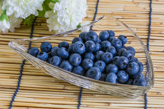 Blueberries in the glass bowl on the wooden background with  white flower. Blueberries in the glass bowl on the wooden background with white flower Stock Images