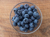 Blueberries in glass cup. On wooden cutting board Stock Image
