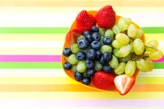 Blueberries, grapes and strawberries in a bowl on a striped tabl Royalty Free Stock Photography