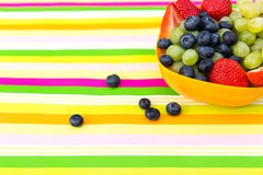 Blueberries, grapes and strawberries in a bowl on a striped tabl Royalty Free Stock Images