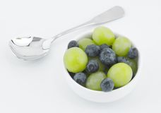 Blueberries and Grapes in White Bowl with Spoon Two Royalty Free Stock Photography