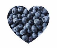 Blueberries in heart shape isolated on a white. Fresh Blueberry Background. Texture blueberry berries close up. Stock Photos