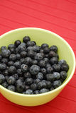Blueberries In Green Bowl Over Red Royalty Free Stock Image