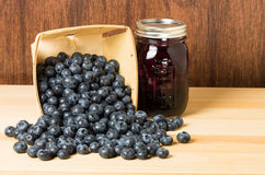 Blueberries and jam or jelly. Blueberries spilling from wooden container with jar of fresh blueberry jam royalty free stock photo