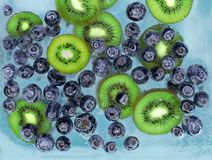 Blueberries and kiwi sinking into blue water with air bubbles royalty free stock photo