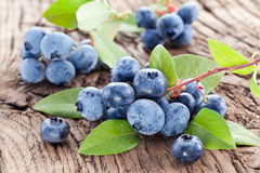 Blueberries with leaves on a wooden table. Royalty Free Stock Photo