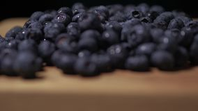 Blueberries lying on a wooden table. Blueberries close-up. Camera`s rotate. 4K.  stock video