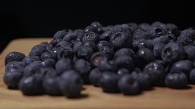 Blueberries lying on a wooden table. Blueberries close-up. Camera`s rotate. 4K.  stock footage