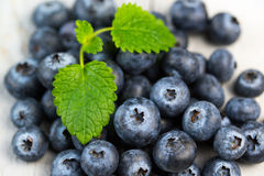 Blueberries and mint leaves close up. On a wooden background Stock Images