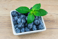 Blueberries with mint leaves. Dewy fresh blueberries in white squared bowl on vintage wooden background royalty free stock photo