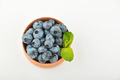 Blueberries and mint leaves in wooden bowl isolated on white Royalty Free Stock Photography