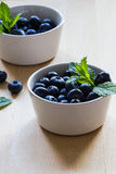 Blueberries and mint in white bowls on a wooden background Stock Photo