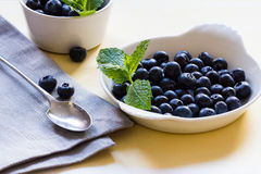 Blueberries and mint in white bowls on a yellow background Stock Images