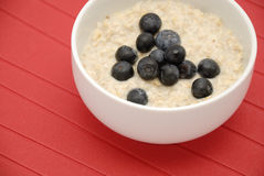 Blueberries and oatmeal in white bowl Stock Photos