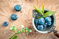 Blueberries in an old metal ladle and leafs Royalty Free Stock Photo