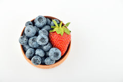 Blueberries and one strawberry in wooden bowl isolated on white Stock Photo