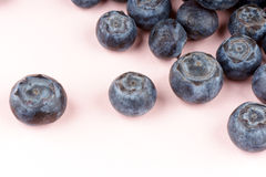 Blueberries over pink. Close-up of some blueberries over a pink paper background. Selective soft focus Stock Photo