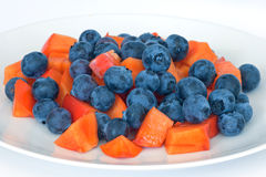 Blueberries and persimmon fruit on plate Royalty Free Stock Photo