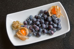 Blueberries And Physalis. A dish of blueberries garnished with physalis Stock Photography
