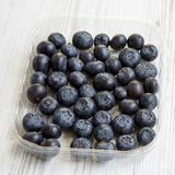 Blueberries in a plastic box over white wooden background, side view. Close-up royalty free stock photo