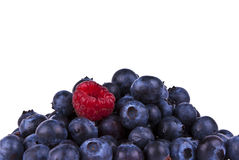 Blueberries & Rasberry isolated with clipping path. Mountain of Blueberries with single Rasberry standing out from the crowd isolated with clipping path Stock Photo