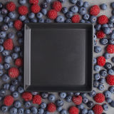 Blueberries and raspberries around a bowl on rusty grey background. Top view Royalty Free Stock Photo