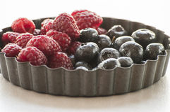Blueberries and Raspberries in the black vintage metal bowl Stock Images