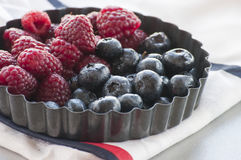 Blueberries and Raspberries in the black vintage metal bowl. On a rustic wooden board Stock Photo