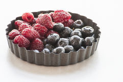 Blueberries and Raspberries in the black vintage metal bowl. On a rustic wooden board Stock Photos