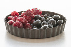 Blueberries and Raspberries in the black vintage metal bowl. On a rustic wooden board Stock Images