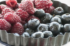 Blueberries and Raspberries in the black vintage metal bowl. On a rustic wooden board Royalty Free Stock Photography