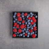 Blueberries and raspberries in a bowl on rusty grey background. Top view Royalty Free Stock Photography