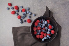 Blueberries and raspberries in a bowl on rusty grey background. Top view Stock Photos