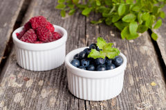Blueberries and raspberries bowl on wooden table. Close up Stock Photo