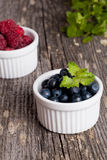 Blueberries and raspberries bowl on wooden table. Vertical Royalty Free Stock Photos