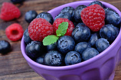 Blueberries with raspberries in a ceramic bowl on table. Blueberries with raspberries in a ceramic bowl on wooden table Stock Images