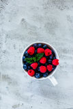 Blueberries and raspberries. Ceramic cup with assortment berries blueberries and raspberries over concrete textured background. Top view composing Royalty Free Stock Images