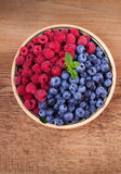 Blueberries and raspberries in clay bowl. Freshly picked berries on rustic background. Berry antioxidant superfood, concept for healthy eating. View from above Stock Photography