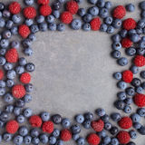 Blueberries and raspberries frame on rusty grey background. Top view Stock Image