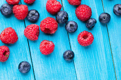 Blueberries and raspberries leaf on wooden table Royalty Free Stock Images