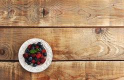 Blueberries and raspberries with mint in bowl. On wooden background - top view copyspace Stock Photos